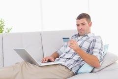 Man shopping online through laptop using credit card Stock Photo