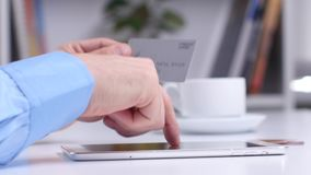 Man shopping online using digital tablet and gold credit card. Close up stock footage