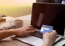 Man shopping online wiht credit card and entering infometion on. Man shopping online with credit card and entering infometion on keyboard at coffee shop Stock Photo