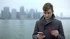Man shopping over the Internet by using his smartphone and credit card near Hudson river stock footage