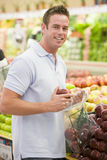 Man shopping in produce section. Of supermarket Royalty Free Stock Images
