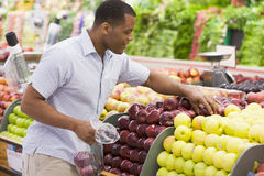 Man shopping in produce section stock photography