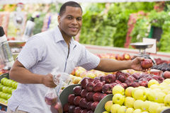 Man shopping in produce section Stock Images