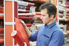 Man shopping red wallpapers in DIY shop. For construction Royalty Free Stock Photo
