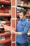 Man shopping red wallpapers in DIY shop. For construction Stock Image