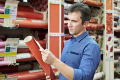 Man shopping red wallpapers in DIY shop. For construction Stock Photo