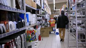 Man shopping in supermarket checking contents of