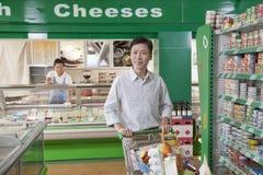 Man shopping in supermarket, pushing cart, Beijing Royalty Free Stock Images