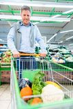 Man shopping in supermarket pushing his trolley with vegetables stock photography