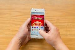 Man shopping till och med mobil på Taobao på kinesisk online-shoppingdag på November 11 Royaltyfria Foton
