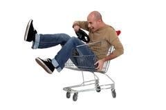 Man in a shopping trolley. Man racing a shopping trolley Stock Photo