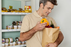 Man shopping a vegetables. Man putting some vegetables in his bag Royalty Free Stock Photo