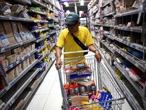 A man shops for food in a grocery store. Stock Image