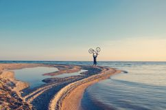 A man on the shore of the bay with a bicycle raised above his he Stock Image