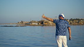 A man on the shore shows something by hand to people on a yacht at sea. man on the beach waving his arms. sea bay stock footage