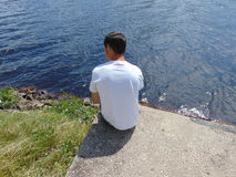 Man on Shore. A young man staring into the water from shore Royalty Free Stock Photo