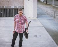 Man in short sleeve shirt holding electric guitar. In the street Royalty Free Stock Photos