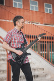 Man in short sleeve shirt playing electric guitar Stock Image