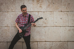 Man in short sleeve shirt playing electric guitar Stock Photography