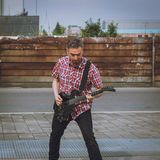 Man in short sleeve shirt playing electric guitar Royalty Free Stock Image