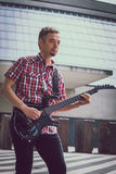 Man in short sleeve shirt playing electric guitar Royalty Free Stock Photos