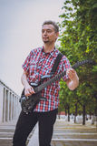 Man in short sleeve shirt playing electric guitar Stock Photo