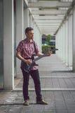 Man in short sleeve shirt playing electric guitar Stock Photos