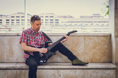 Man in short sleeve shirt playing electric guitar Stock Images