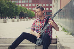 Man in short sleeve shirt playing electric guitar Royalty Free Stock Images