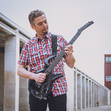 Man in short sleeve shirt playing electric guitar Royalty Free Stock Photo