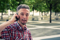 Man in short sleeve shirt talking on phone Stock Images