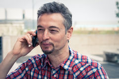 Man in short sleeve shirt talking on phone Stock Image