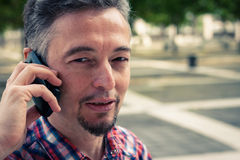Man in short sleeve shirt talking on phone Stock Photo