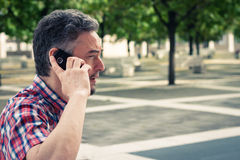 Man in short sleeve shirt talking on phone Royalty Free Stock Photography