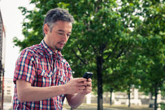 Man in short sleeve shirt texting on phone Stock Photos