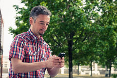 Man in short sleeve shirt texting on phone Royalty Free Stock Photo