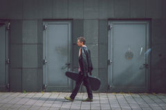 Man in short sleeve shirt walking with guitar case Royalty Free Stock Images