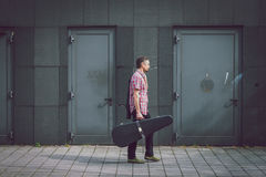 Man in short sleeve shirt walking with guitar case Stock Photography