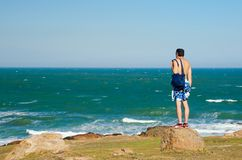 A man with shorts with a bag on his shoulder is standing on a rock and looking at the sea royalty free stock photos