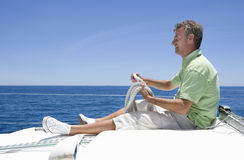 Man in shorts and green polo shirt sitting on deck of sailing boat out to sea, holding rope, smiling, profile Royalty Free Stock Photo