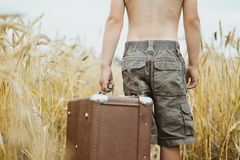 Man in shorts holding retro suitcase in field of Stock Photos