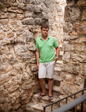 Man in shorts leaning against ancient stone wall Stock Photography