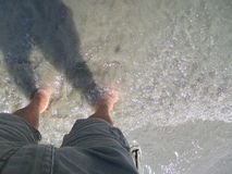 Man in shorts staying in the shallow water Royalty Free Stock Photos