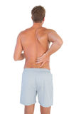 Man with shorts suffering from back pain Royalty Free Stock Photography