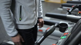 A man in shorts and a sweatshirt is engaged on a treadmill, increasing pace. stock footage