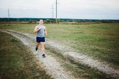 Man in shorts and t-shirt runs along the lake stock photo