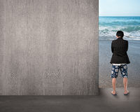 Man in shorts thinking and standing on beach entrance Stock Photos
