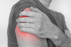 Man with shoulder pain is holding his aching arm. Black and white photo stock photos