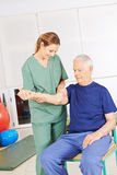 Man with shoulder pain in physical therapy Stock Photo