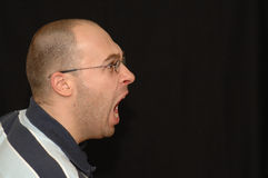 Man shouting. A young adult caucasian white man head profile portrait wearing glasses having an angry expression in his face with open mouth shouting and Royalty Free Stock Photos